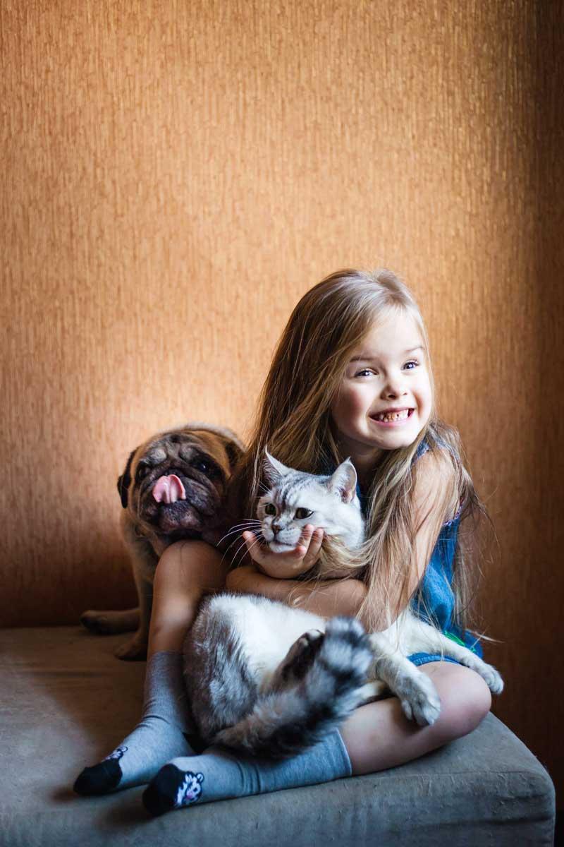 Petite fille souriante assise sur un coussin tenant son chat dans le bras et son chien qui est assis à côté qui se liche le museau. Clinique vétérinaire Lachine