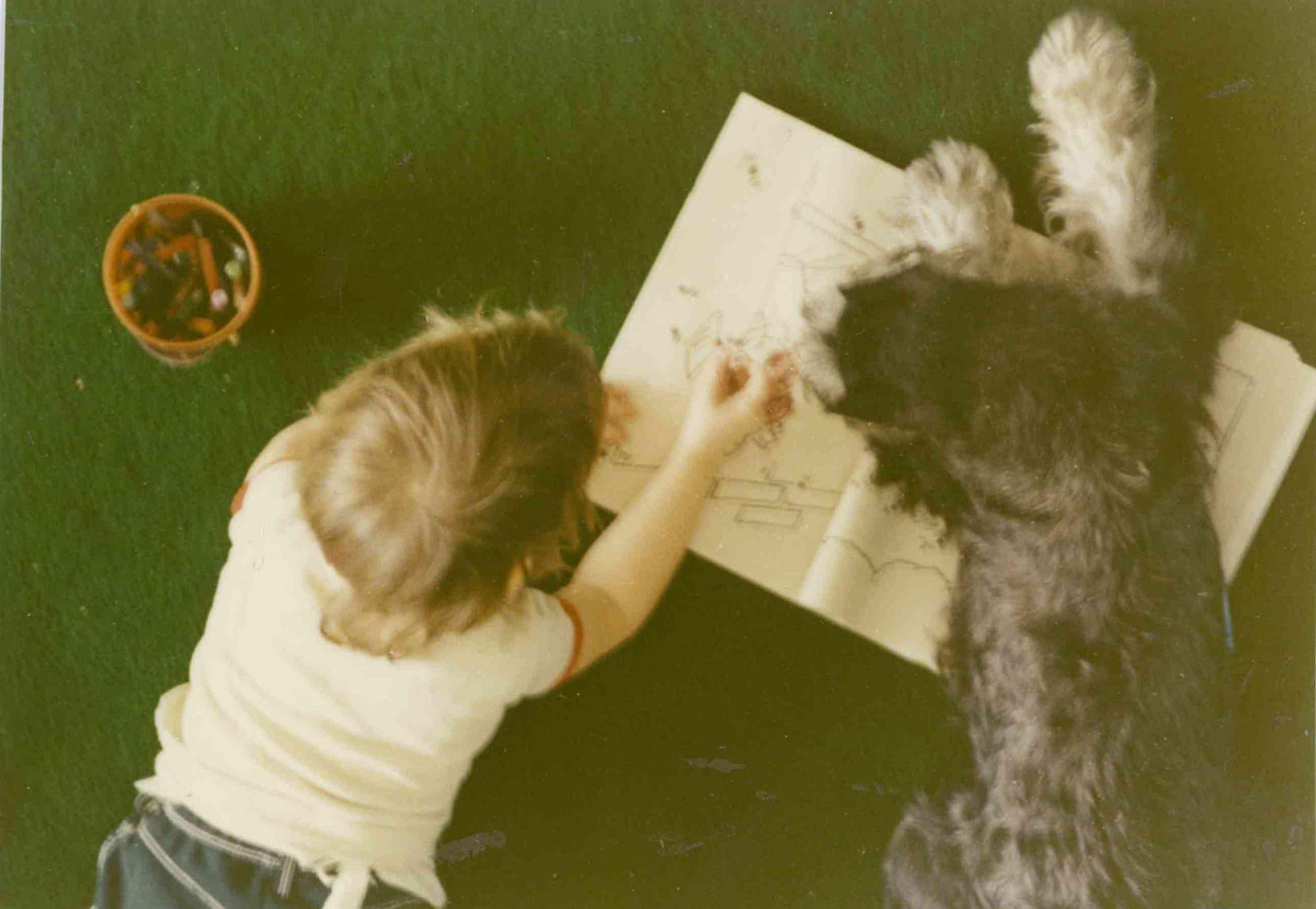 Portrait de Caroline Ferron, enfant, avec son chien en train de dessiner. Clinique vétérinaire Lachine