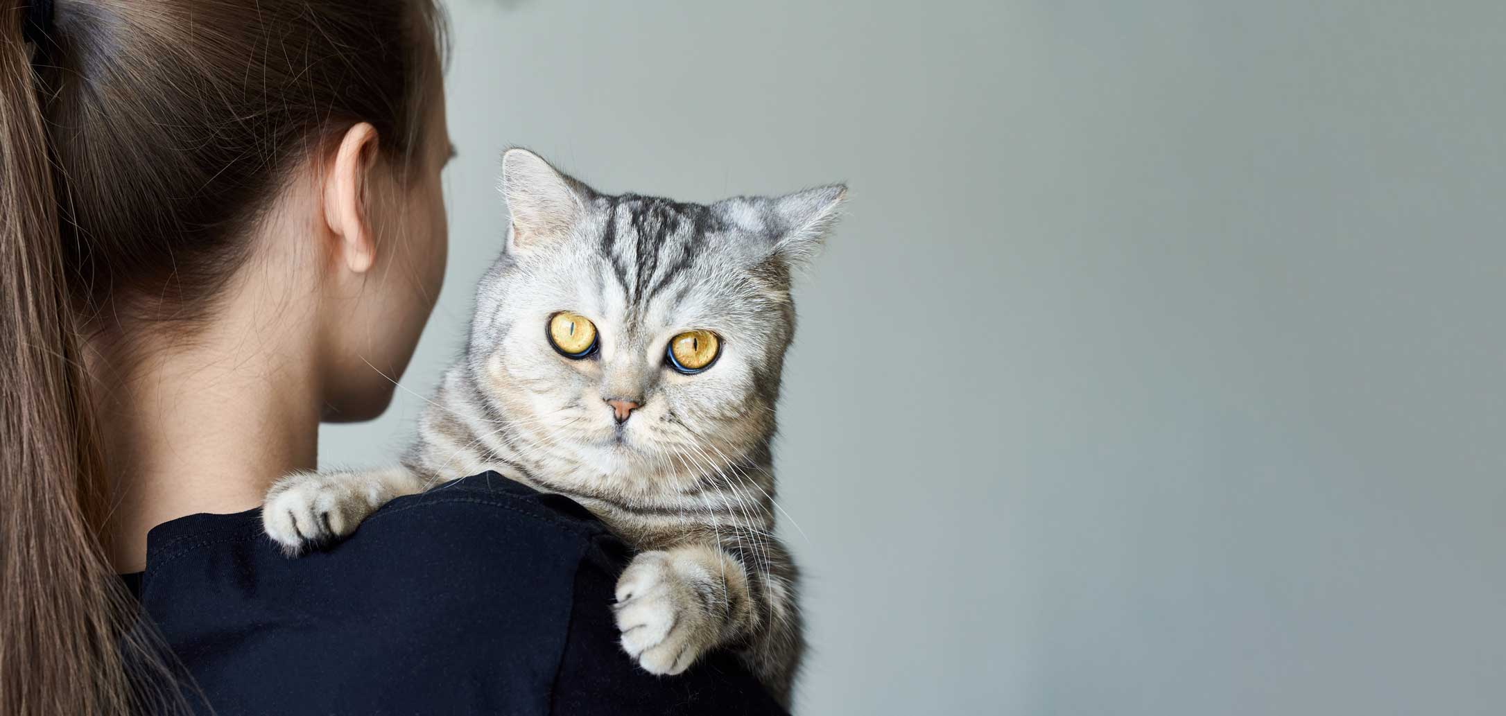 Jeune femme de dos avec un chat sur son épaule. Clinique vétérinaire Lachine