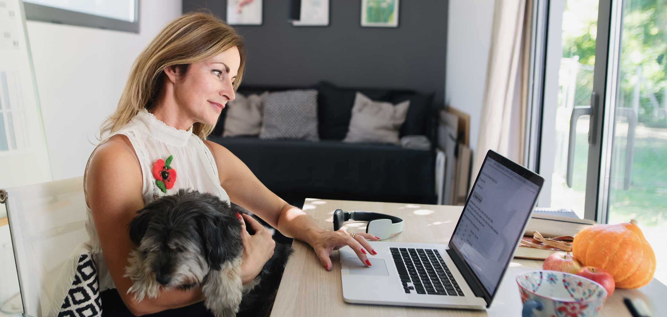 Femme assise à son bureau avec un chien dans les bras en travaillant sur son ordinateur portable. Clinique vétérinaire Lachine